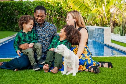 the real haiti pierre-louis family, diana and endy, haitian-american family, italian american family photoshoot, posing with their white poodle in the grass, multicultural family, mixed races, biracial children