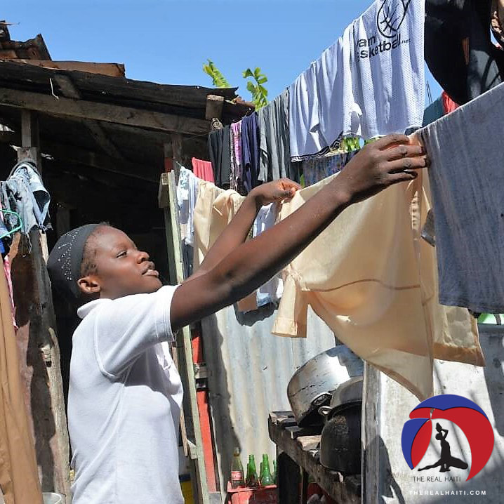 Student hanging up her uniform to dry on a clothes line at home, haitian laundry,back to school in haiti, uniforms, school, education system, ecole, jacmel haiti